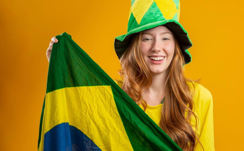 Brazil supporter. Brazilian redhead woman fan celebrating on soccer, football match on yellow background. Brazil colors. Wearing a t-shirt, flag and fan hat.