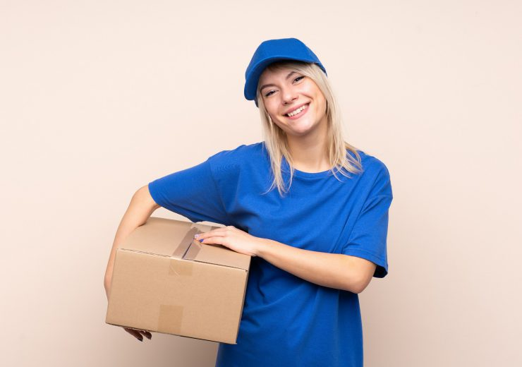 Young delivery woman over isolated background laughing