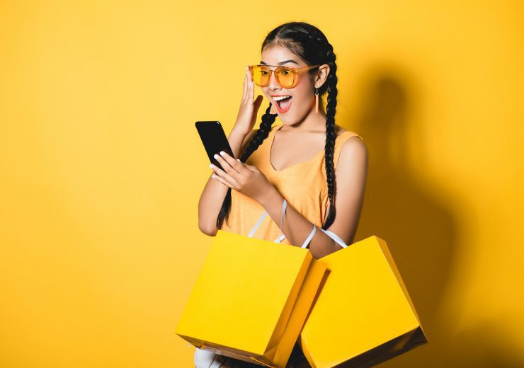 Beautiful young woman with shopping bags using her smart phone o