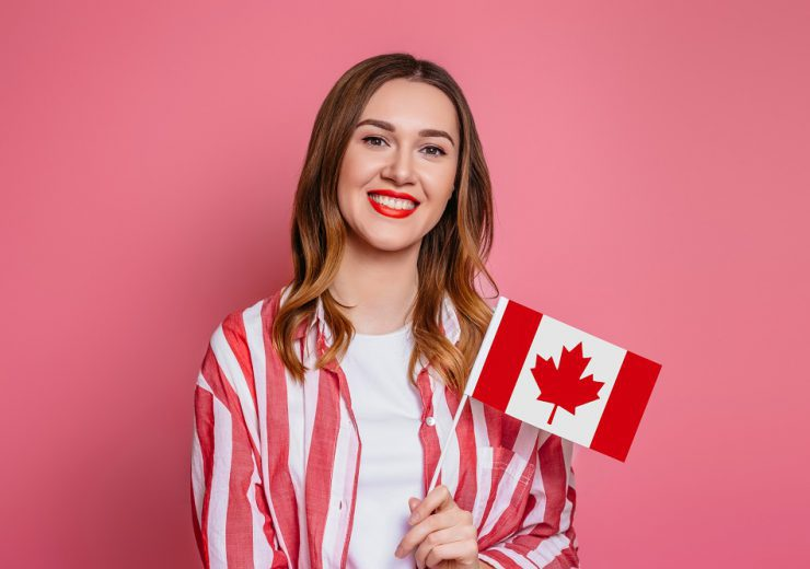 Young woman wearing white T-shirt and striped red shirt smiling and holding a small canada flag and looking at camera isolated over pink background, celebration Canada day, holiday, copy space