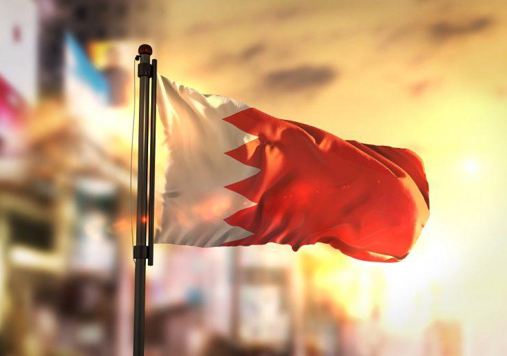 Bahrain Flag Against City Blurred Background At Sunrise Backlight