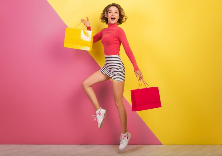 smiling attractive woman in stylish colorful outfit jumping with shopping bags, happy, pink yellow background, polo neck, striped mini skirt, sale, discout, shopaholic, fashion summer trend, emotional